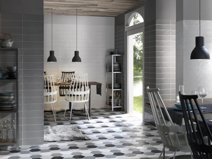 cuisine et salle à manger aux murs blanc et gris avec plafond en bois foncé et revêtement de sol au carrelage design géométrique