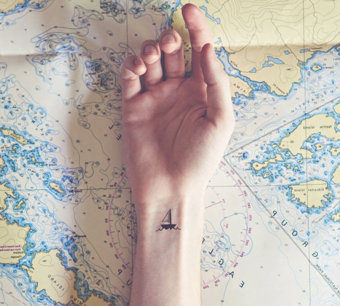 choisir un tattoo simple et petit sur le thème de voyage et aventure, dessin en encre avec mini bateau et vagues de mer