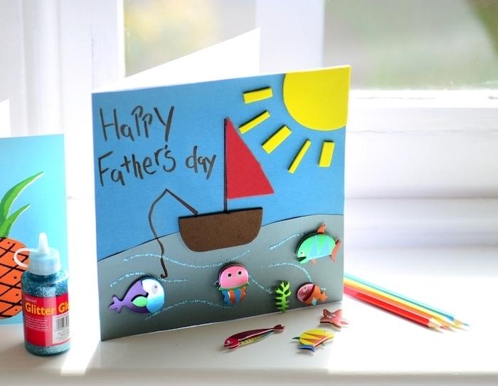 idée comment faire une carte fête des pères maternelle, avec fond bleu paysage marin avec bateau, soleil et animaux de mer en feutrine