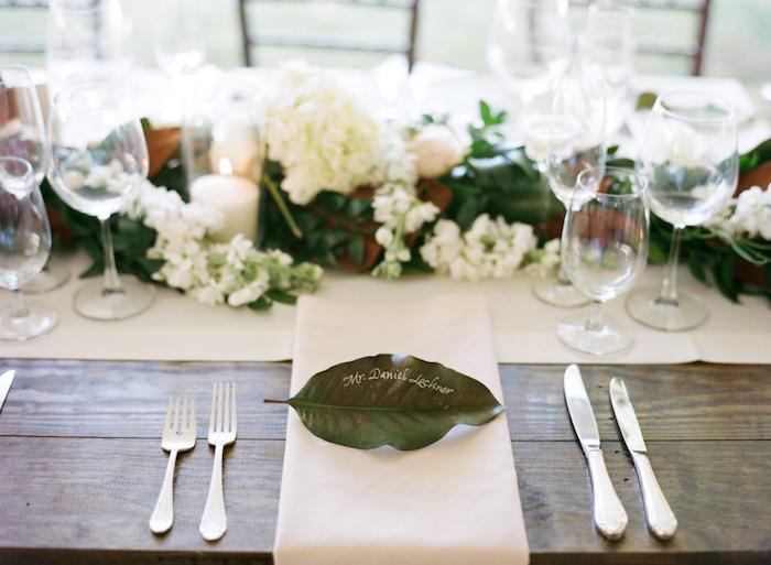feuille verte décorée de nom invité noté au feutre blanc, chemin de table et serviette blanche et table bois brut, centre feuillage et fleurs blanches