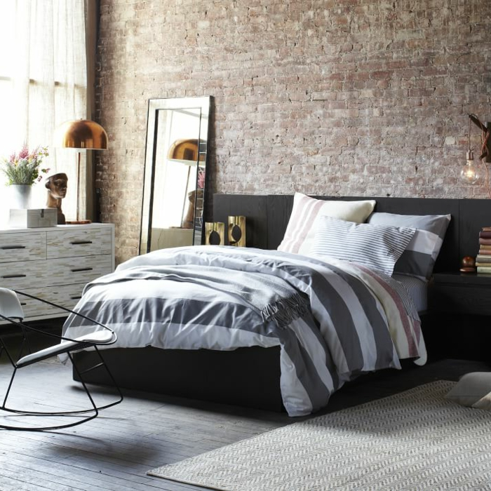 chambre à coucher esprit loft, mur en briques, miroir rectangulaire, meuble de rangement en bois, lampe cuivrée