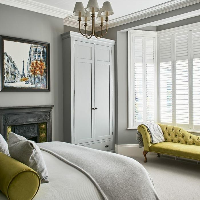 sofa baroque en couleur moutarde dans une chambre à coucher adulte moderne, plafonnier baroque, armoire grise, peinture de la tour eiffel