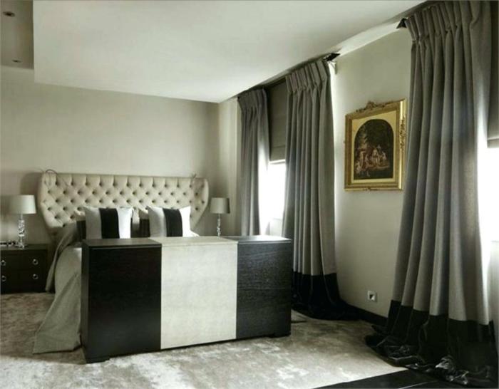 une chambre en style imposant, lit avec tête de lit baroque, rideaux gris, peinture à l'encadrement doré et tapis gris