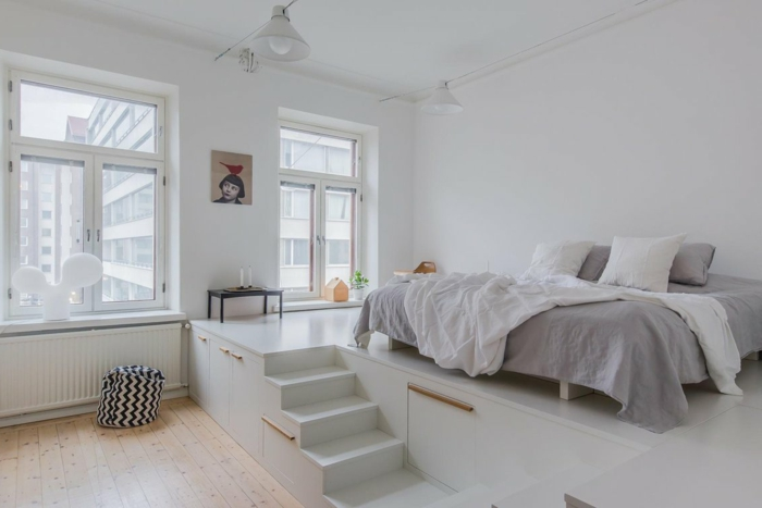 jolie chambre à coucher blanche et grise, escalier blanc et petite estrade pour le lit