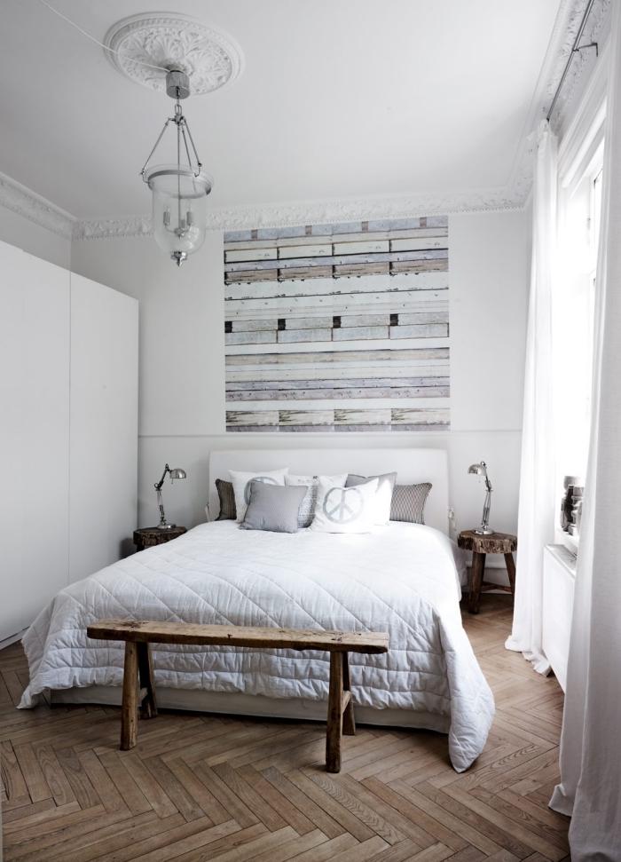une chambre à coucher d'esprit scandinave rustique où la tete de lit papier peint effet planches de bois semble prolonger visuellement le lit