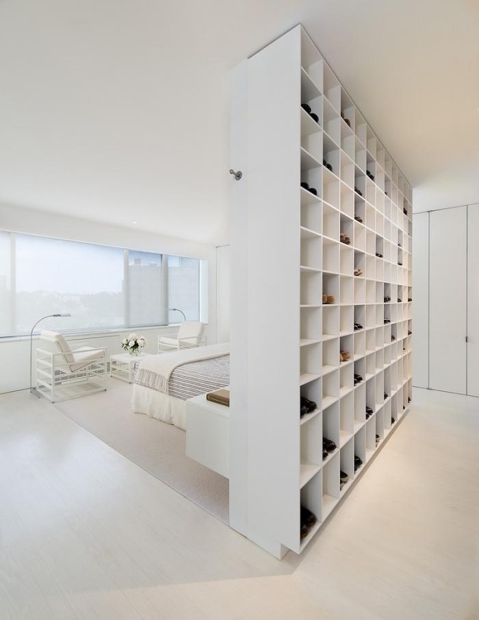 un meuble de séparation dans la chambre à coucher jouant le rôle d'une étagère à chaussures