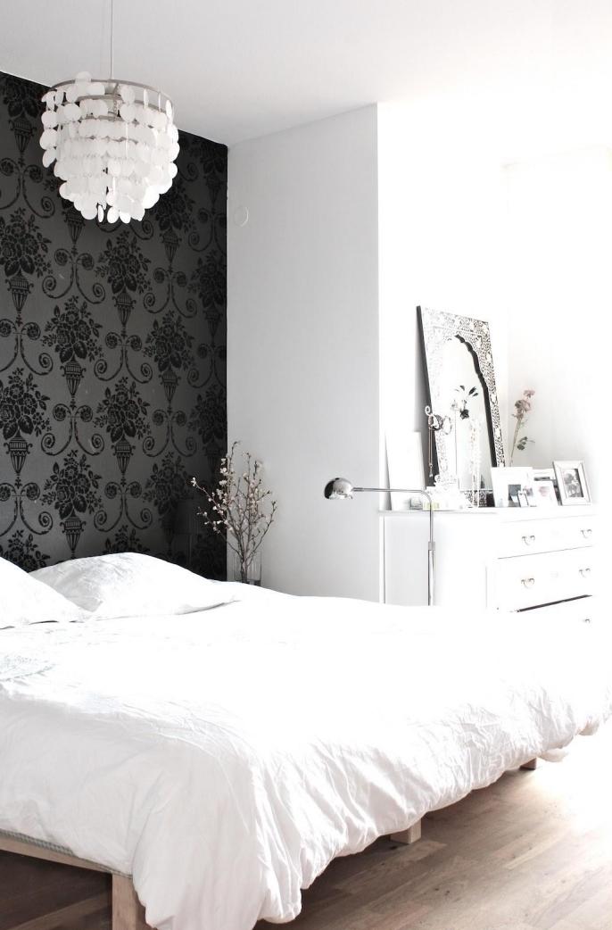 créez un mur d'accent unique dans la chambre à coucher qui fait office de tete de lit deco, un joli contraste entre l'intérieur blanc et le papier peint intissé noir