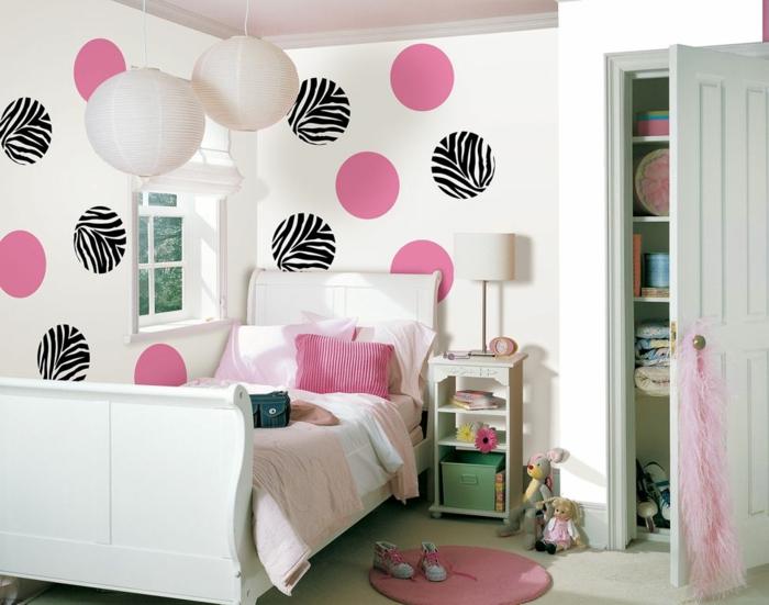 chambre a coucher moderne, idée déco chambre, murs blancs avec des grands pois roses et noirs et blancs, petit tapis rose, grand placard avec porte blanche, peluches lapinous a cote du meuble de chevet