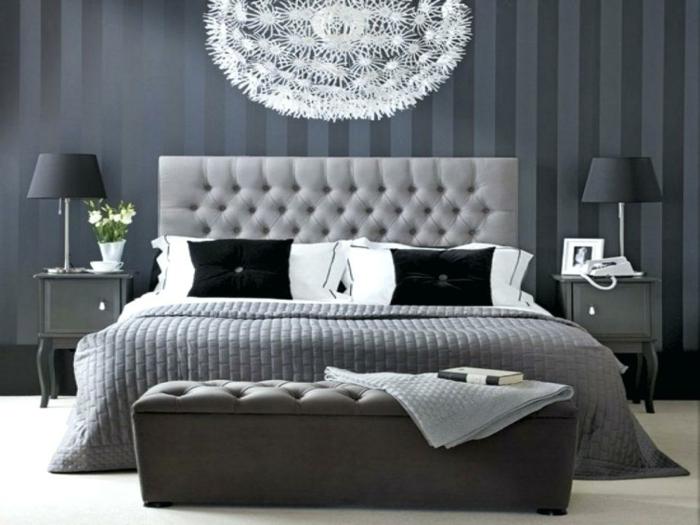 chambre en gris et blanc décorée d'un grand plafonnier blanc, plaid de lit gris, deux chevets noirs