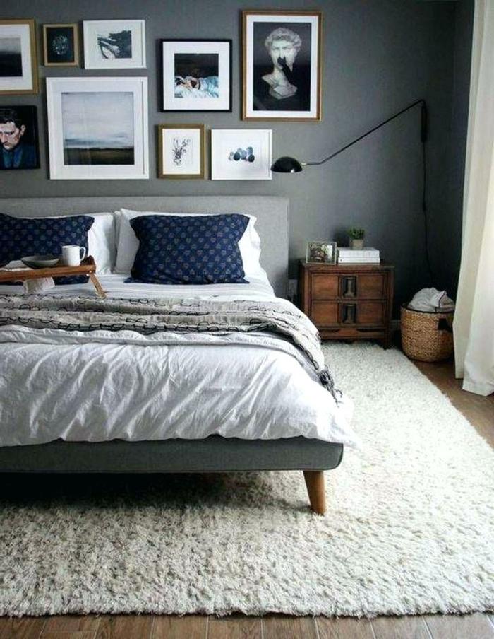 tapis blanc dans une chambre grise, cadres photos, chevet en bois, panier rustique, lampe de sol