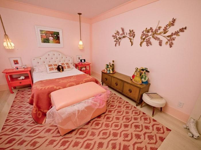 tapis en nuances rouges et pêche, motifs branches d'arbres sur les murs, meuble large en bois vintage, tabouret bas en simili cuir couleur ivoire, parquet pvc en couleur ivoire, déco chambre ado fille