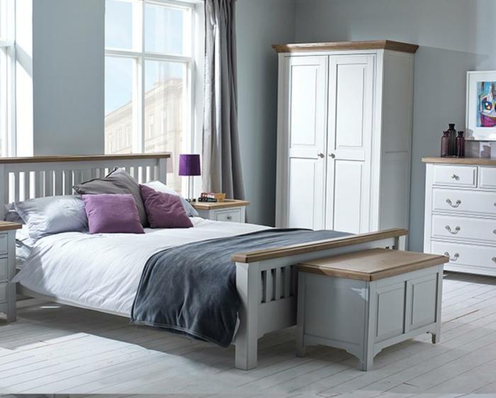 armoire blanche et commode blanche, banquette de lit avec rangement; planches de bois au sol