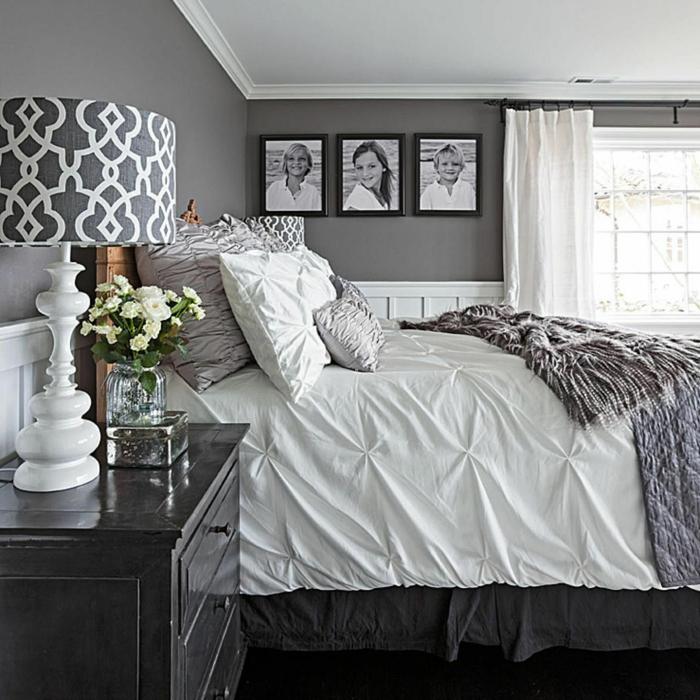 mur gris avec photographies dans une chambre blanche et grise, lampe abat-jour géométrique sur un chevet noir