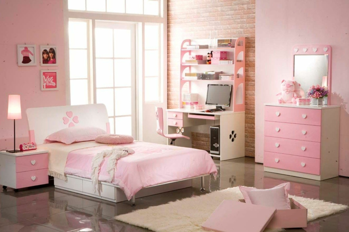 chambre fille ado en rose et blanc, murs roses, meubles roses avec des poignées en forme de cœurs blancs, tapis rectangulaire au poil long, bureau en blanc et en couleur pêche