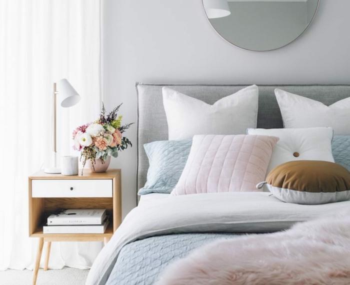 lit gris et blanc, petit chevet en bois et blanc, plusieurs coussins et miroir mural rond