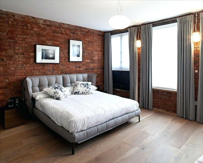chambre en gris, blanc et mur en briques, rideaux gris, sol en bois, appliques murales