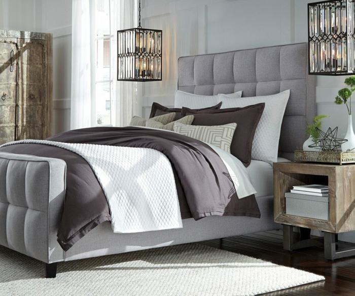 chambre à coucher en blanc et gris avec une tete de lit grise, lanternes pendantes, tapis blanc, chevet en bois