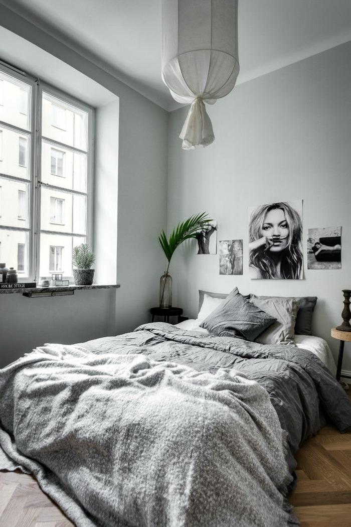 plafonnier original, chambre boho chic avec portrait de femme, mur gris, linge de lit en gris et blanc