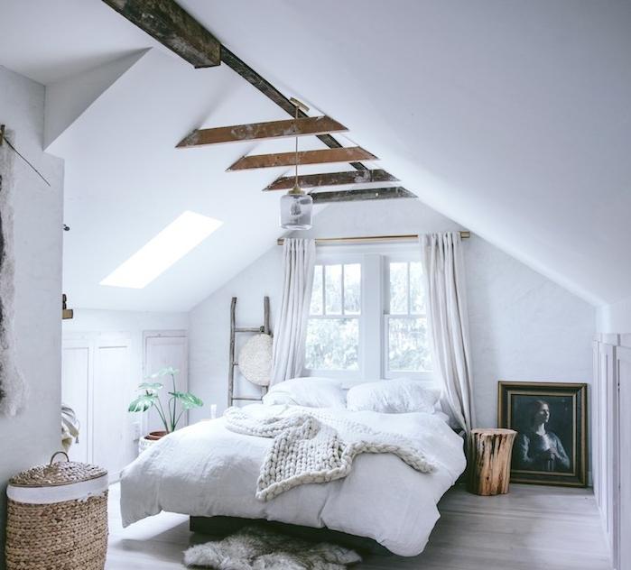 déco chambre sous comble, avec des poutres apparentes, linge de lit blanc, echelle decorative, parquet gris clair, plante verte, cadre peinture portrait