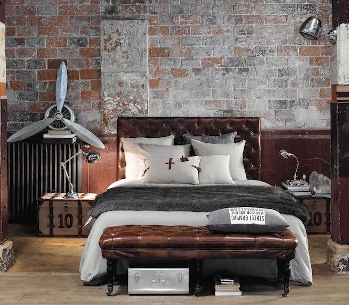 mur de briques defraichi, lit en cuir, linge de lit gris et blanc, table de nuit en cagette industrielle, lampe industrielle