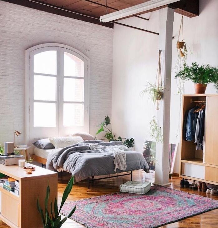 idée de déco chambre style industriel décorée de mur en briques, lit en bois et métal, poutres apparentes, parquet marron, tapis oriental, armoire et commode bois, plantes vertes