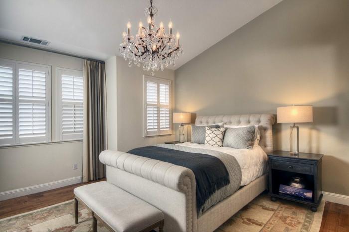 déco chambre adulte en couleurs neutres, chandelier en cristal, banquette de lit grise, tapis beige, deux lampes de chevet beiges