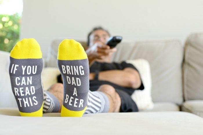 exemple de cadeau DIY facile avec une paire de chaussette en gris et jaune décorée de lettres amusantes sur le thème bière