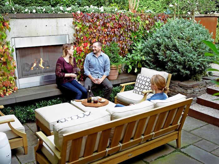 exemple d aménagement jardin terrasse en béton avec cheminée extérieure, salon de jardin en bois, coussins d assise blanc cassé, mur végétal extérieur