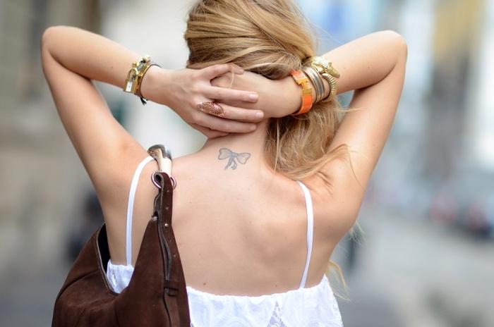 idée pour un tatouage nuque à design discret, femme aux cheveux longs et blonds avec petit tattoo en forme de ruban sur le nuque