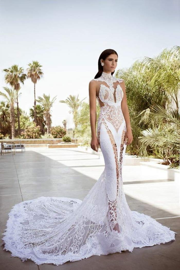 robe de mariée moulante, robe sirène dentelle, traîne longue, transparence pleine sur les jambes en longueur et sur la partie en éventail, dentelle blanche sur le col qui se prolonge sur les épaules