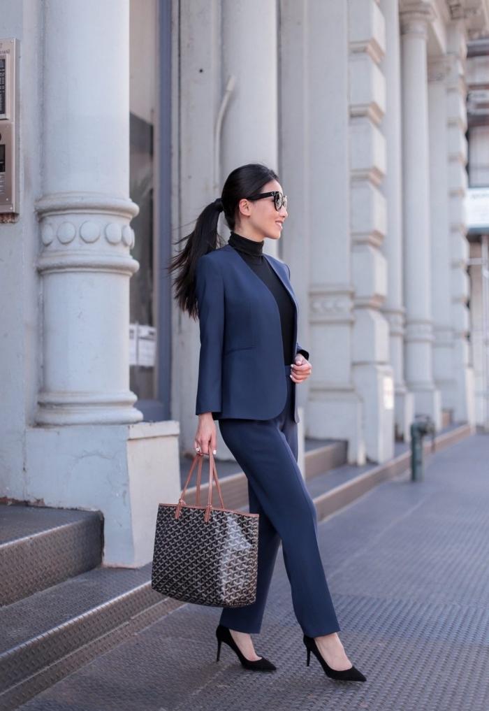 exemple de tailleur pantalon femme chic de couleur bleu foncé porté avec un pull élégant en noir et chaussures à petits talons
