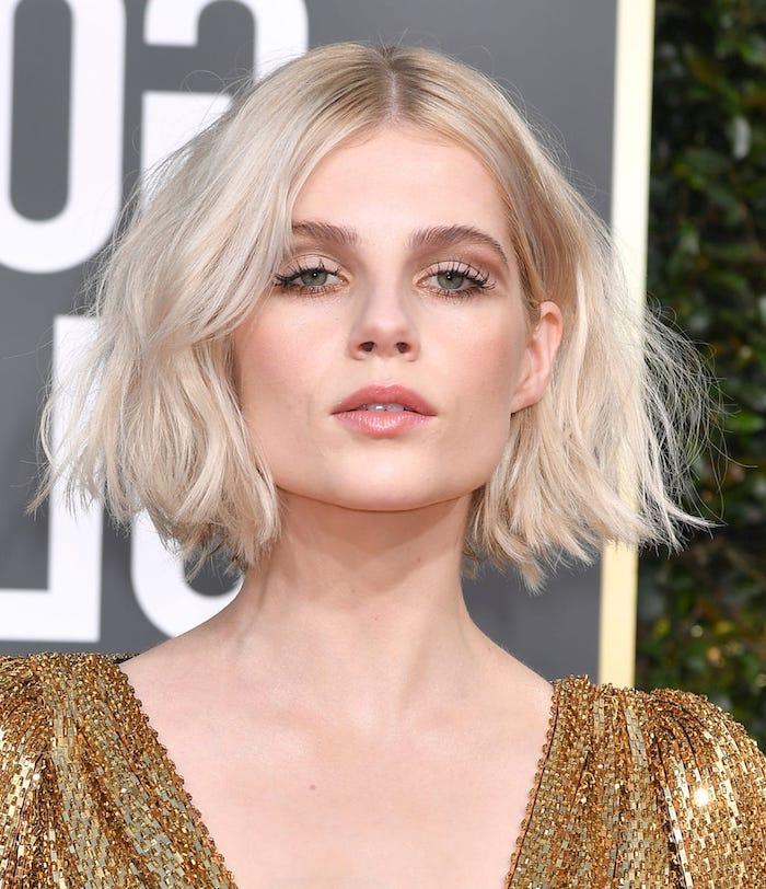 coupe de cheveux carré volumineux sur cheveux blond platine aspect décoiffé et raie au milieu, robe de soirée chic couleur or
