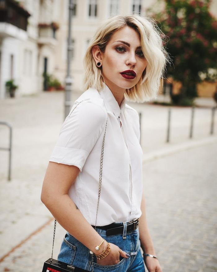 coloration blonde et sur cheveux coupés en ccarré plongeant mi long avec des ondulations subtiles, tenue stylée femme en chemise blanche et jean
