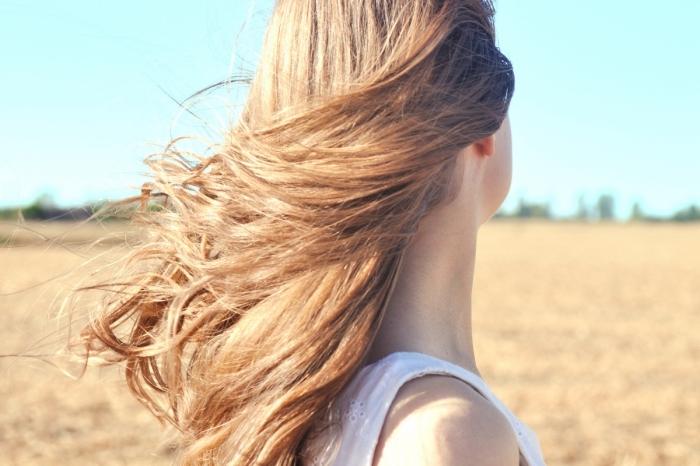 cheveux longs et sains de couleur châtain aux reflets caramel, effet rayons du soleil pour éclaircir naturellement ses cheveux