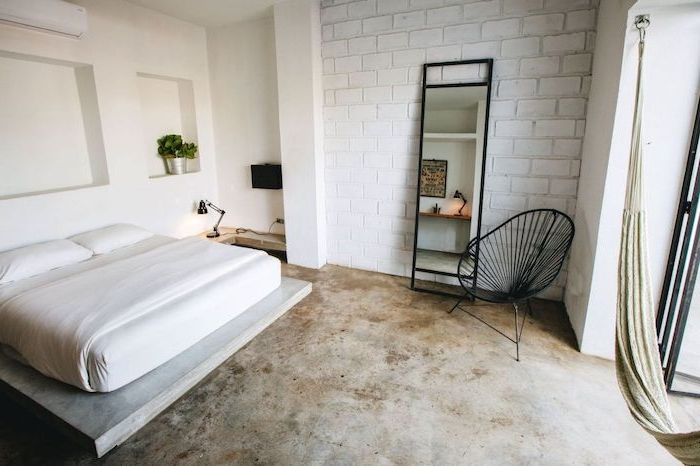 matelas blanc sur plate forme bois, sol effet béton, mur en briques blanches, chaise industrielle noire, niches murales
