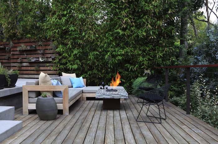 idée terrasse bois avec canapé bois, table basse avec braséro intégré, clôture bois végétalisée