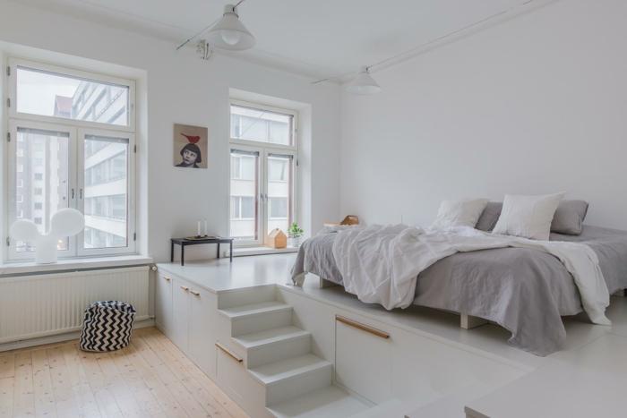 petit escalier blanc dans la chambre à coucher, lit gris et blanc, sol en planches, lampe design indistriel