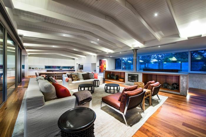 idées pour décorer son salon, tapis gris, grands fauteuils en cuir, petites tables basses, plafond en bois peint blanc