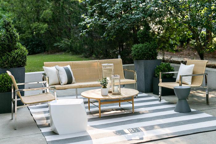 deco terrasse avec revetement en beton, table basse bois, tapis gris et blanc, canapé et chaises rotin et metal, buis en bacs à fleurs