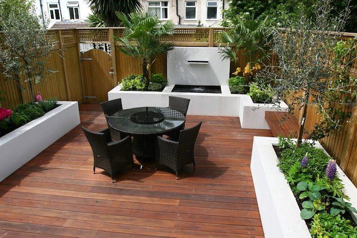 deco terrasse simple avec coin repas en table et chaises noires, bacs à fleurs blancs en béton avec végétation