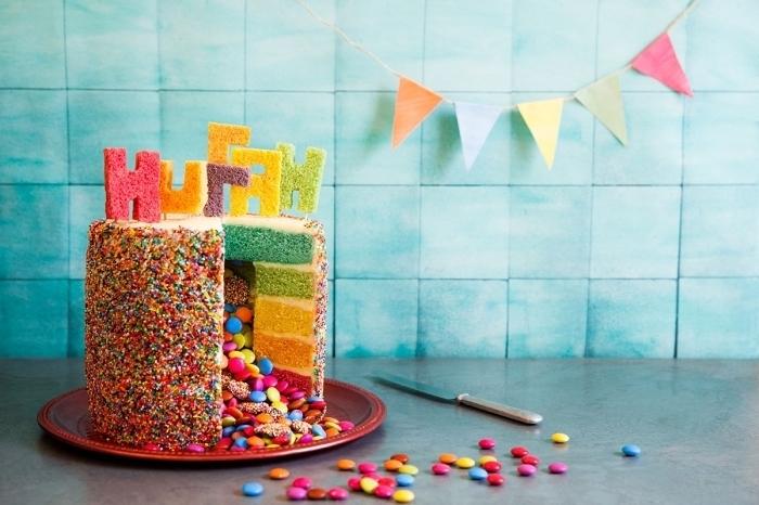 recette de gateau au smarties façon piñata cake décoré avec des vermicelles colorées et des lettres découpées dans les génoises colorées