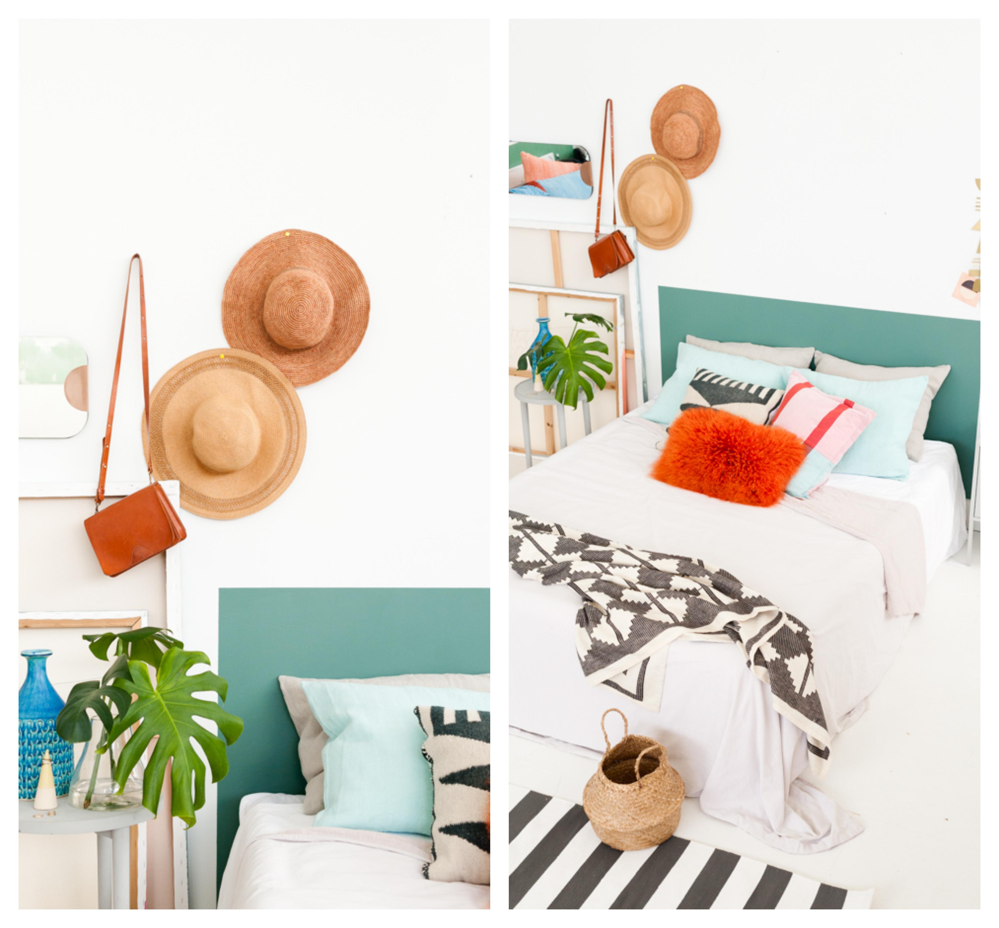 deco tete de lit en peinture vert foret, coussins décoratifs, linge de lit noir et blanc, deco chapeaux, vase et plantes sur une table de nuit blanche