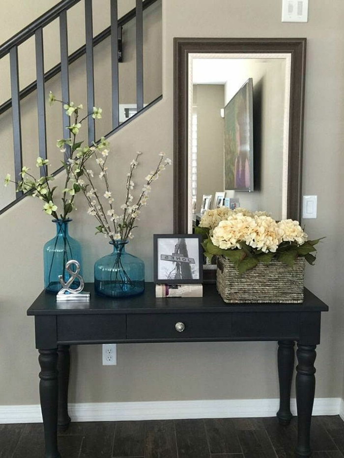 un hall d'entrée de maison moderne, vases bleus transparents, panier avec pivoines blanches
