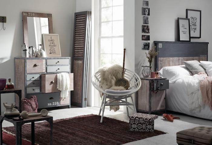modele de commode industrielle avec nombreux tiroirs, linge de lit gris, blanc et rose sur un lit bois décoré de peinture ardoise, deco murale graphique, tapis marron, chaise blanches scandinave