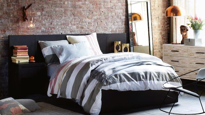 mur de briques avec lit gris foncé, linge de lit gris et blanc, commode industrielle bois et métal noire, lampes décoratives