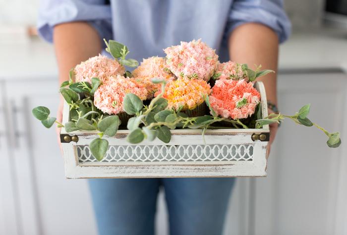 une jolie composition florale hors du commun réalisée avec des cupcakes en forme de fleurs dans un panier vintage, activite fete des meres pour réaliser un cadeau gourmand