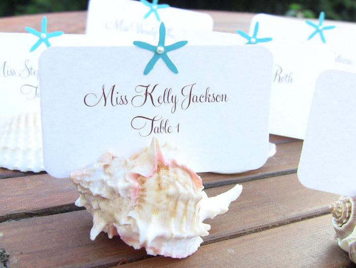 exemple de deco de table mariage bord de mer avec coquille de mer et une étiquette blanche inséré, déco étoile bleue