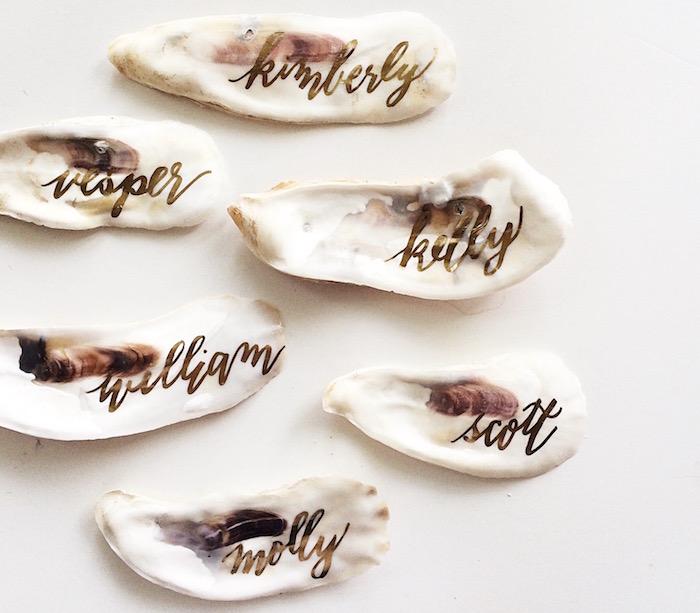 coquille de mer décorée de texte or écrit dessus, porte nom mariage style bord de mer original