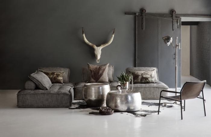 ambiance rustique dans un salon vaste aux murs gris foncé et plancher blanc avec canapé d'angle foncé et tapis imitation peau animale