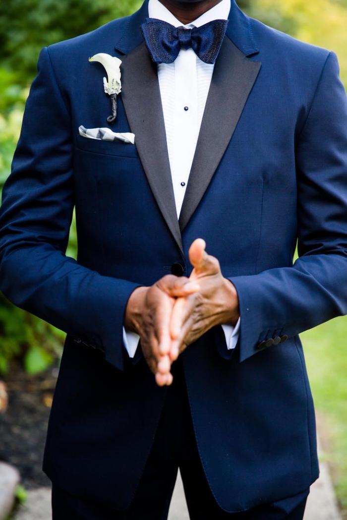 tenue mariage homme formelle en smoking bleu marine avec revers contrasté en satin noir assorti avec un noeud papillon satiné